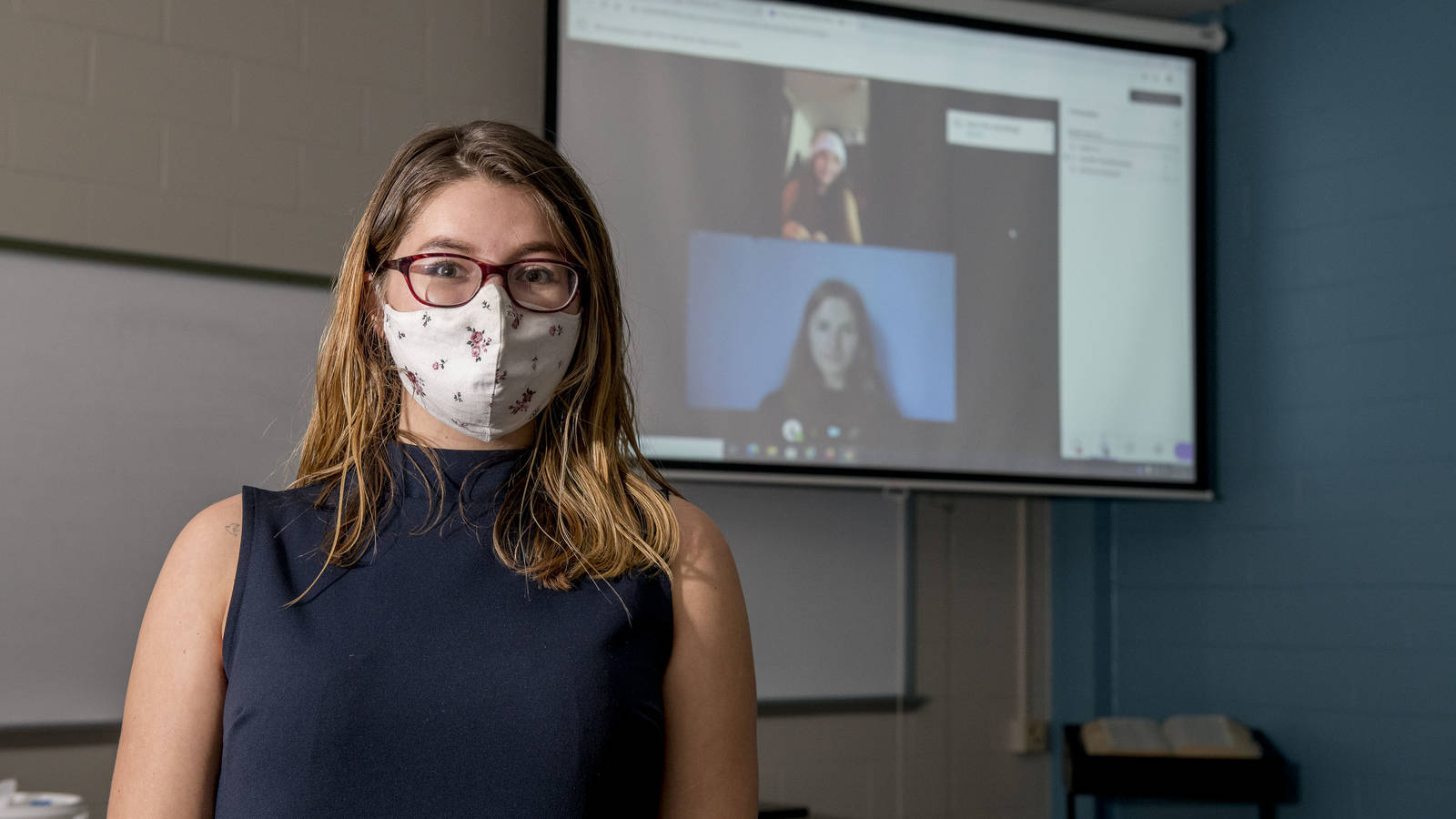 Female students in lab, one masked two on remote screen
