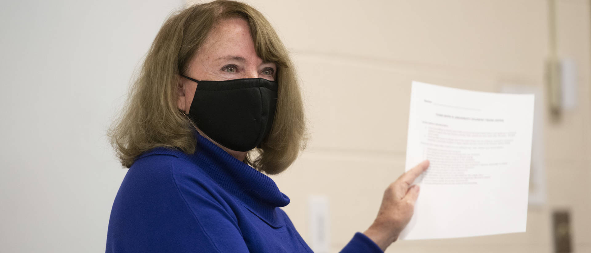 Instructor in mask holding up a paper while addressing class