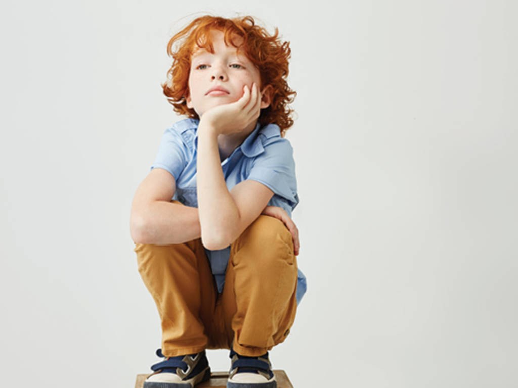 red-haired child crouching down thinking