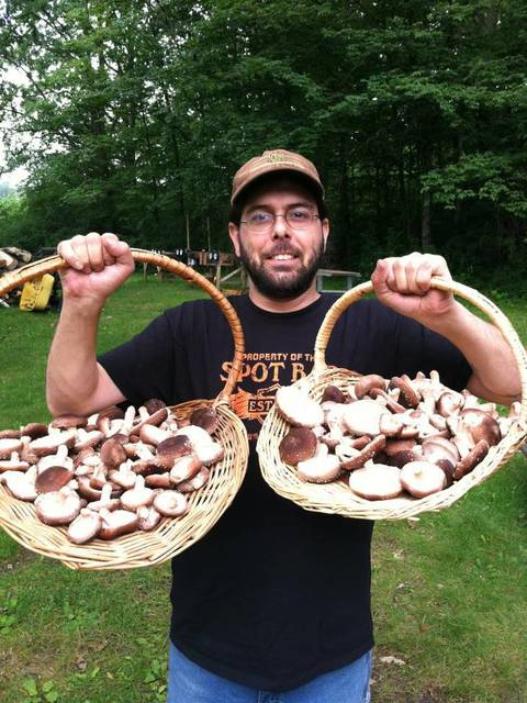 man holding two baskets of wild mushrooms