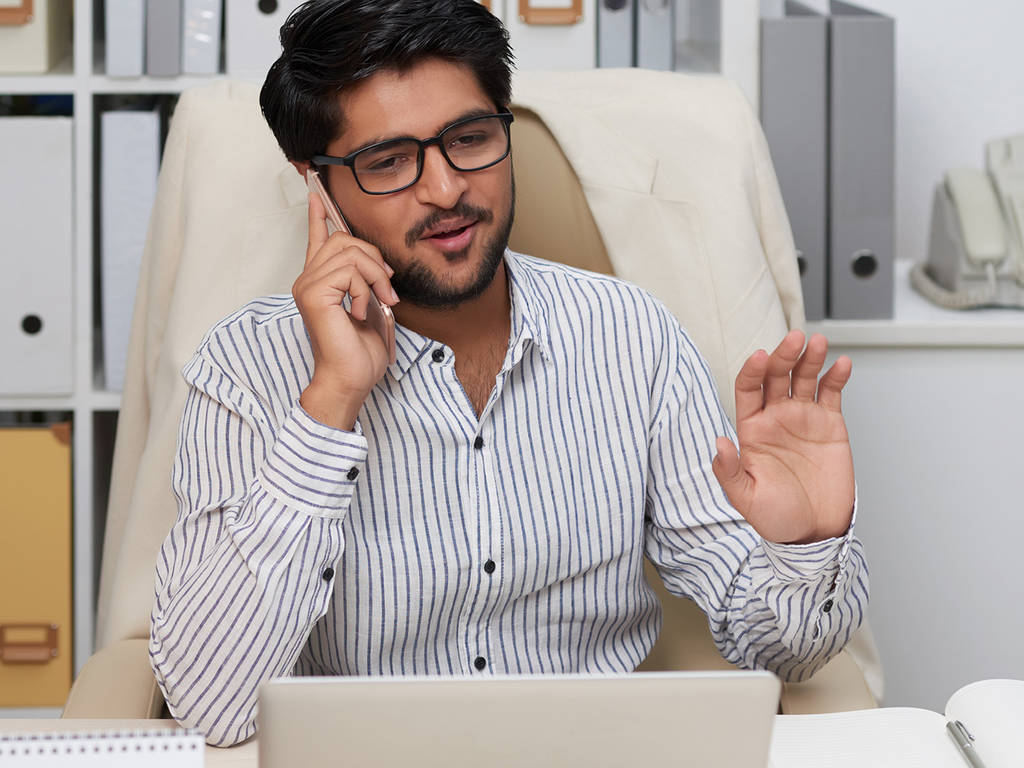 person using a cell phone and using a computer