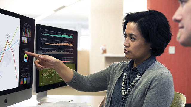 Data Science instructor pointing at a computer screen with a graph with student sitting next to her