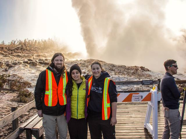 UW-Eau Claire grad Mara Reed (right) stands in front of Steamboat Geyser in Yellowstone National Park. Reed's research about geyser's more frequent eruptions is gaining national attention. (Photo by Carol Beverly)