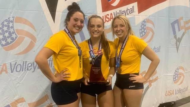 Three volleyball players posing with award.