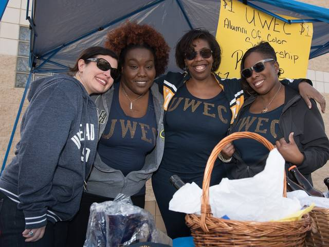 Members of the Alumni of Color Network operate a raffle at the 2015 Homecoming game to raise money for the organization's Social Justice and Inclusion Scholarship.