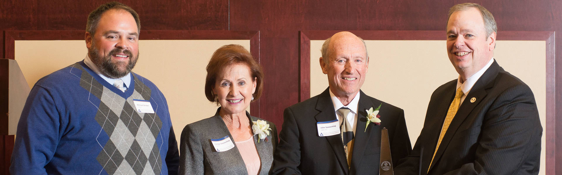 Then-UW-Eau Claire Alumni Board Chair Michael Strubel, left, and Chancellor Jim Schmidt present Carolyn ('67) and John Sonnentag ('66) with the Lifetime Excelllence Award.