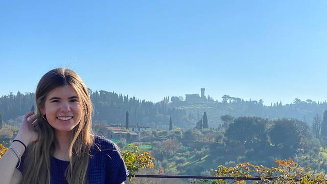 Fall 20 Library scholarship winner Audrey standing in front of a beautiful green landscape