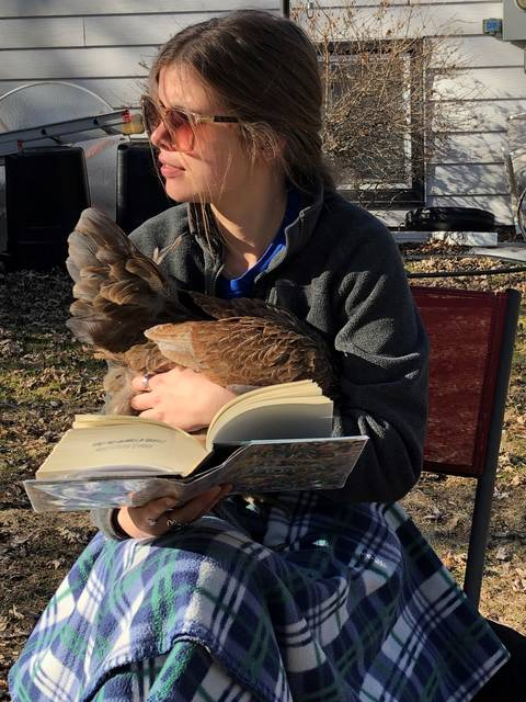 Audrey wearing sunglasses and holding a book and her pet chicken in her lap, on top of a plaid blanket