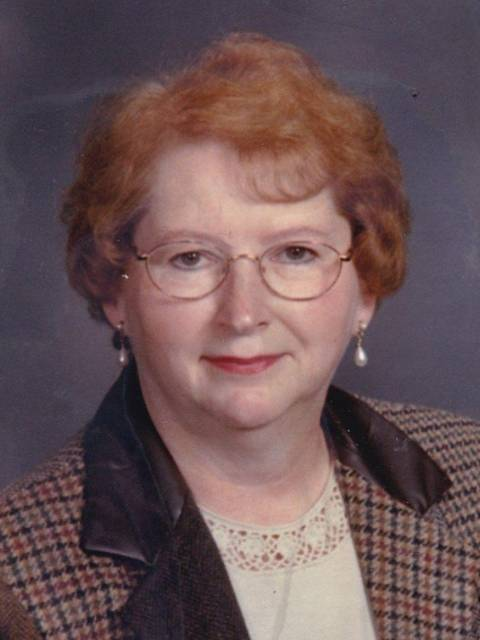 A formal university head shot photo of Cotsy Jones, where she is seated in front of a textured background