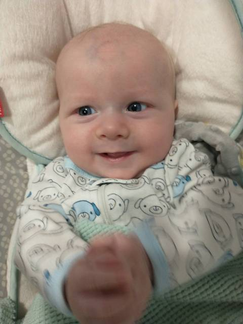 A baby, Ansel Lewis, laying down in a blanket and smiling at the camera