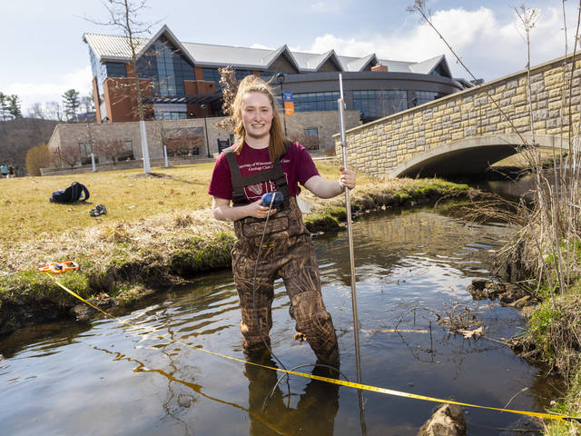 Senior Katherine Langfield collects research samples in Little Niagara Creek on lower campus. Langfield, who will graduate in May with a degree in geology, says research has been a big part of her undergraduate education at UW-Eau Claire.