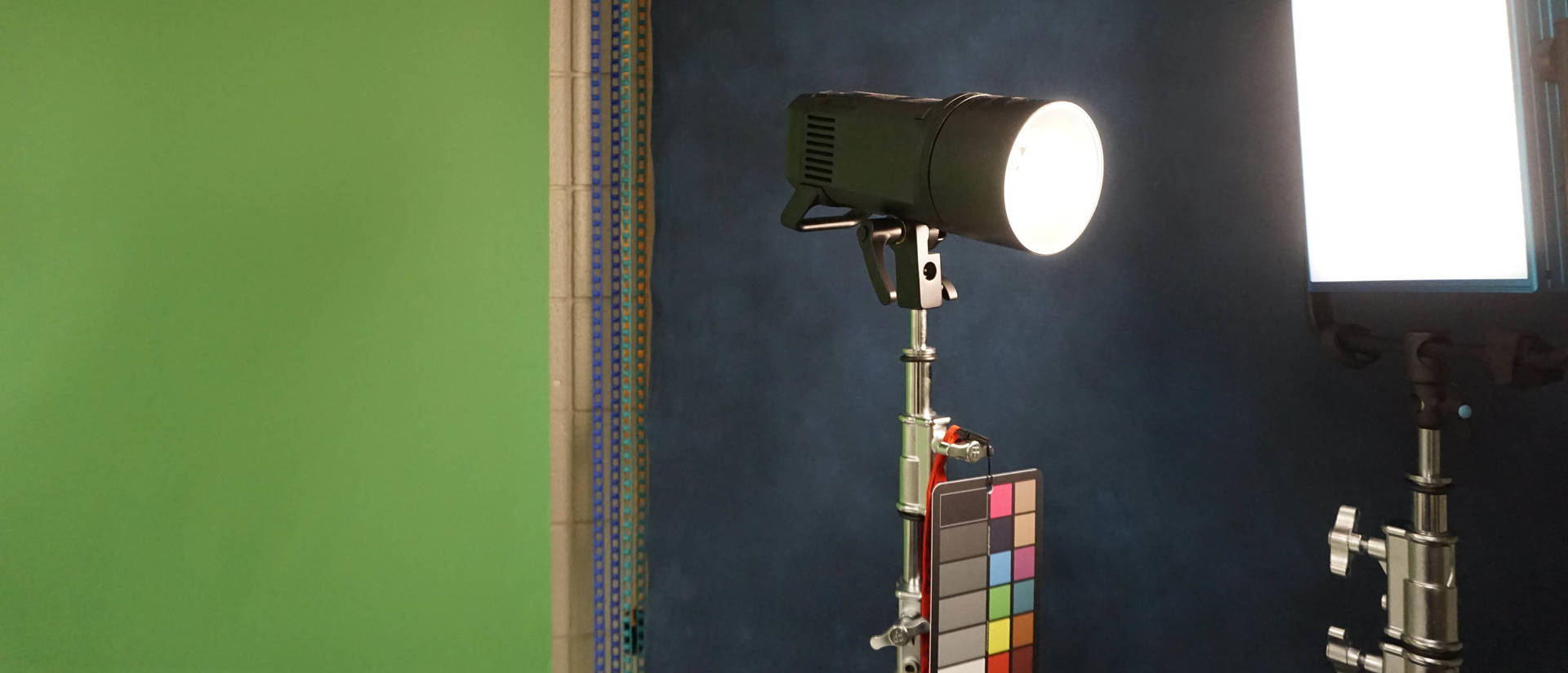 Two photography lights against a green screen