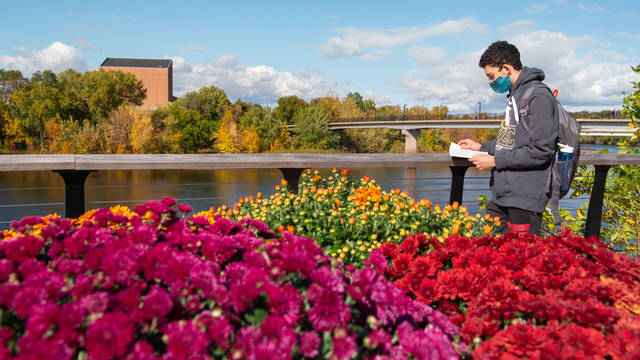 Student wearing a mask looks at textbook in front of spring flowers and the Chippewa River.
