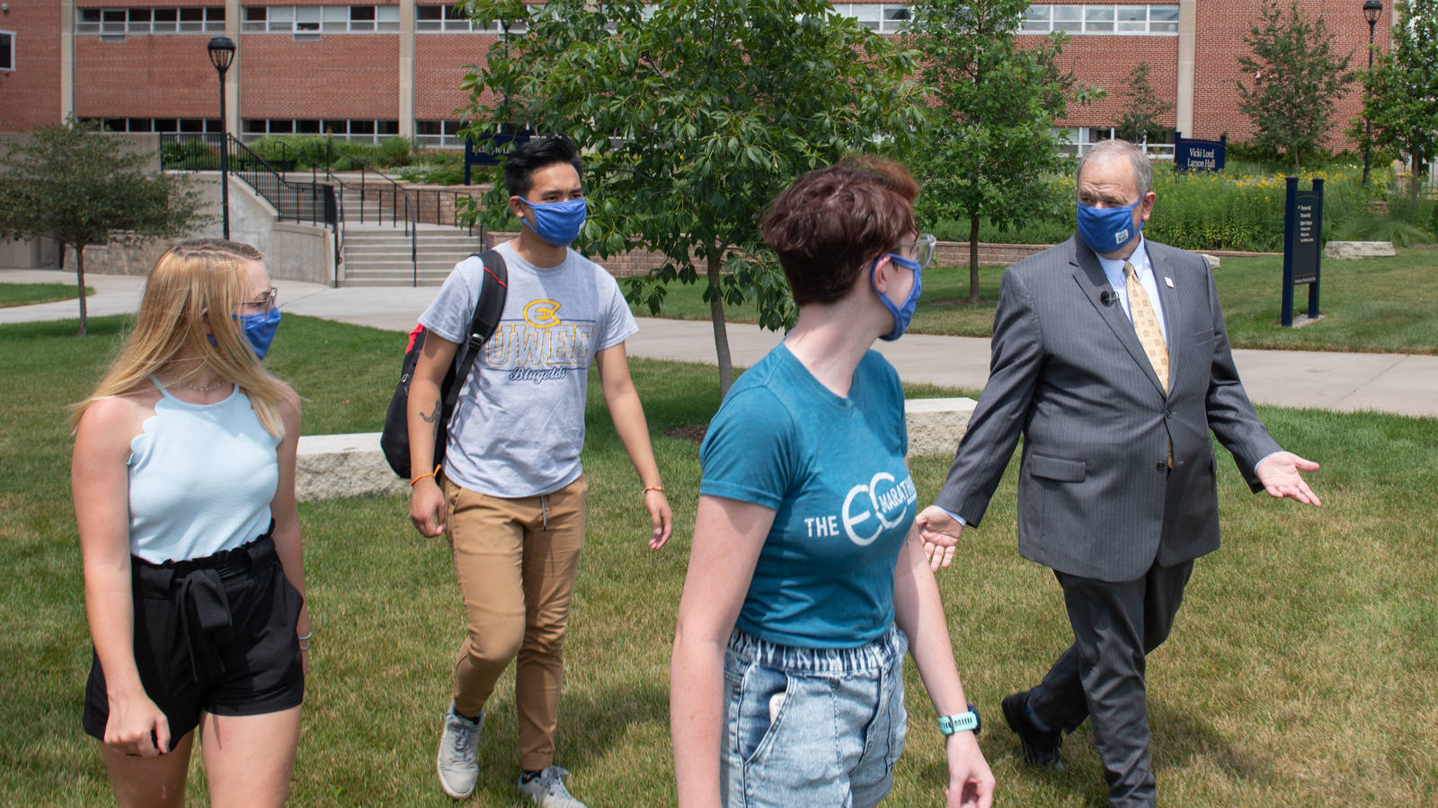 Chancellor Schmidt walks on campus with students pre-reopeing, waering masks