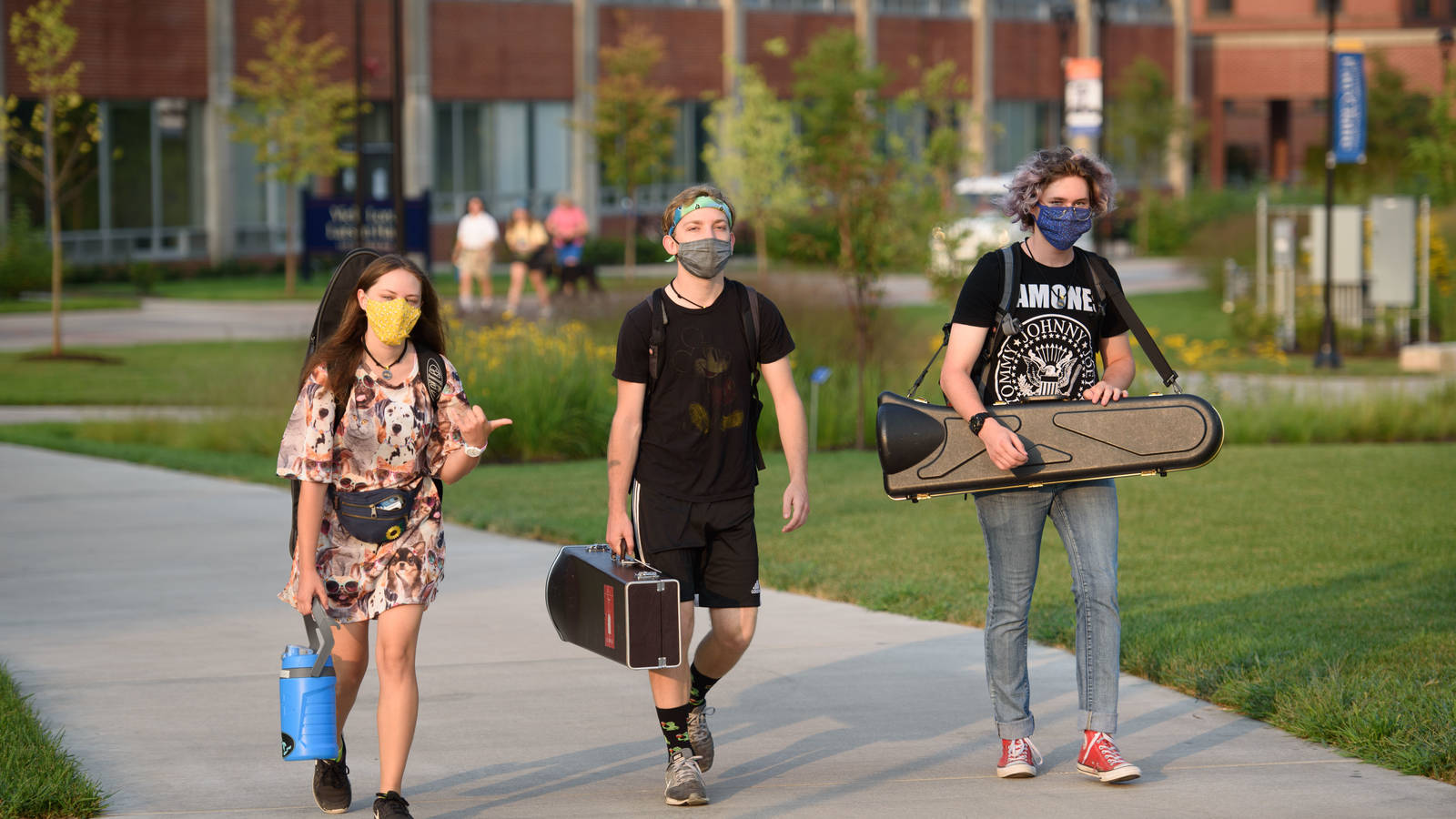 students carrying cased instruments outside