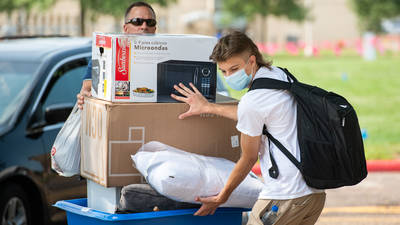 Students moving into dorms, masks on