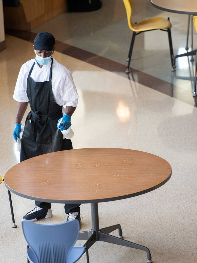 Student worker cleaning tables in Davies Marketplace