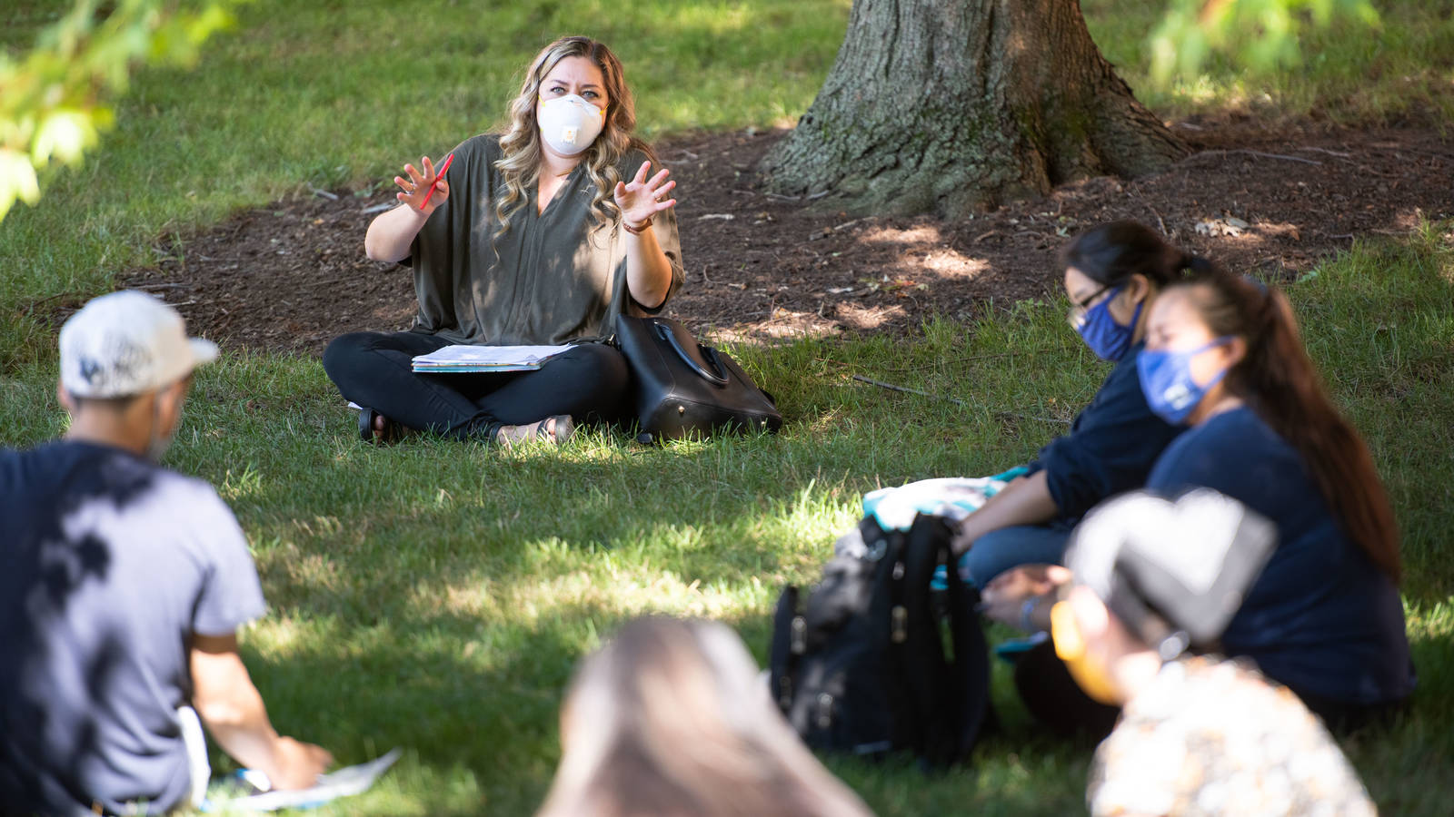 Outdoor class session, students sitting on grass
