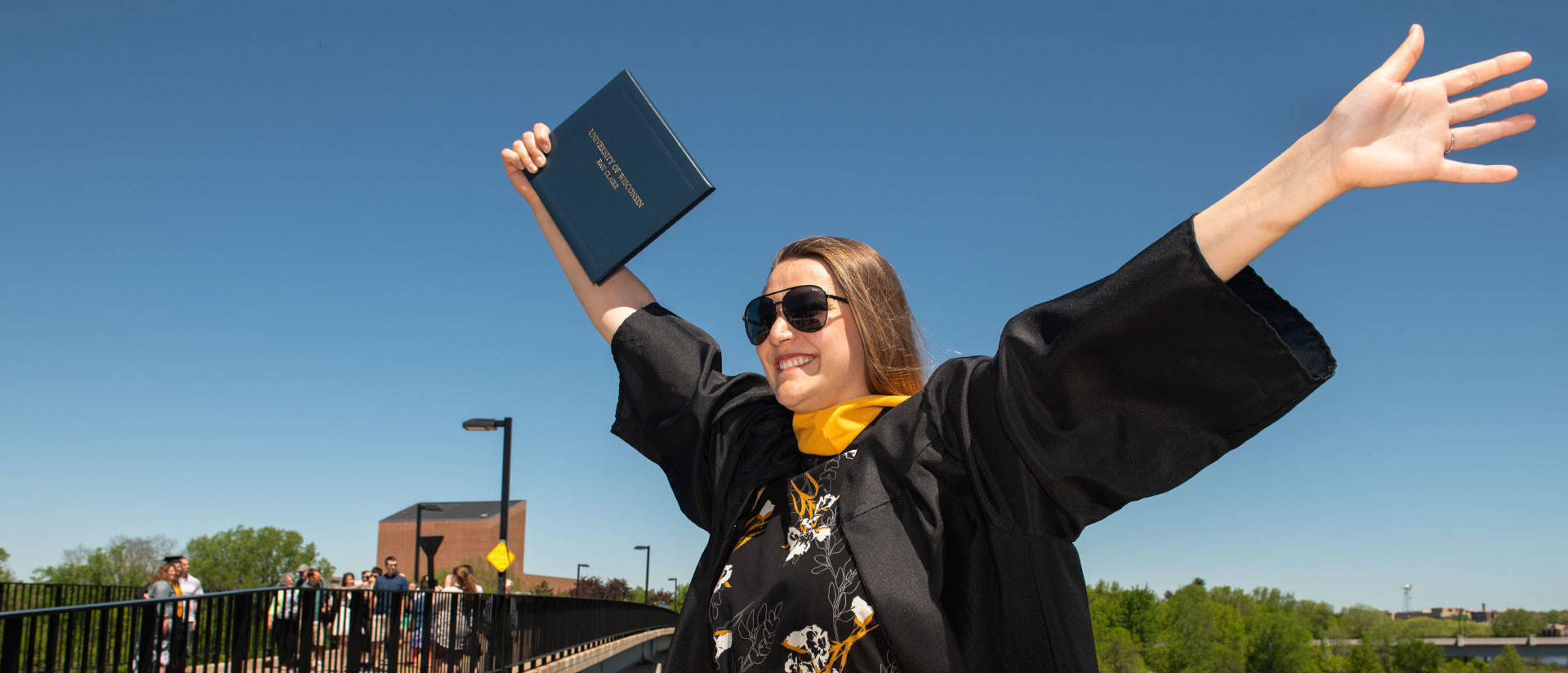 Photo of undergraduate outside in sunglasses holding bachelor's degree diploma in the air