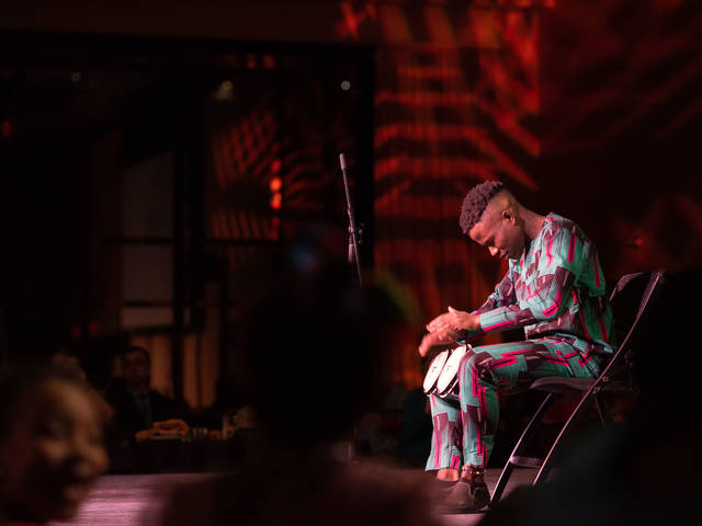 Olu Famule drumming on a stage in Nigerian traditional clothing