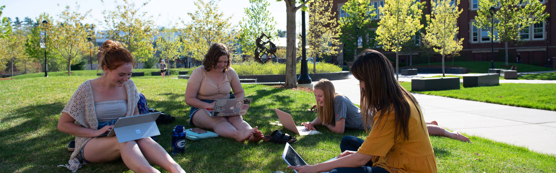 Four students are gathered in the grass, smiling and studying.