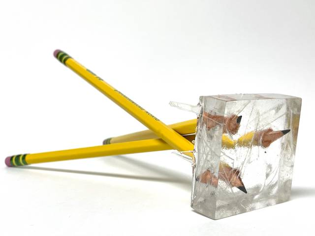 Three No.2 pencils stabbing into a clear block of resin