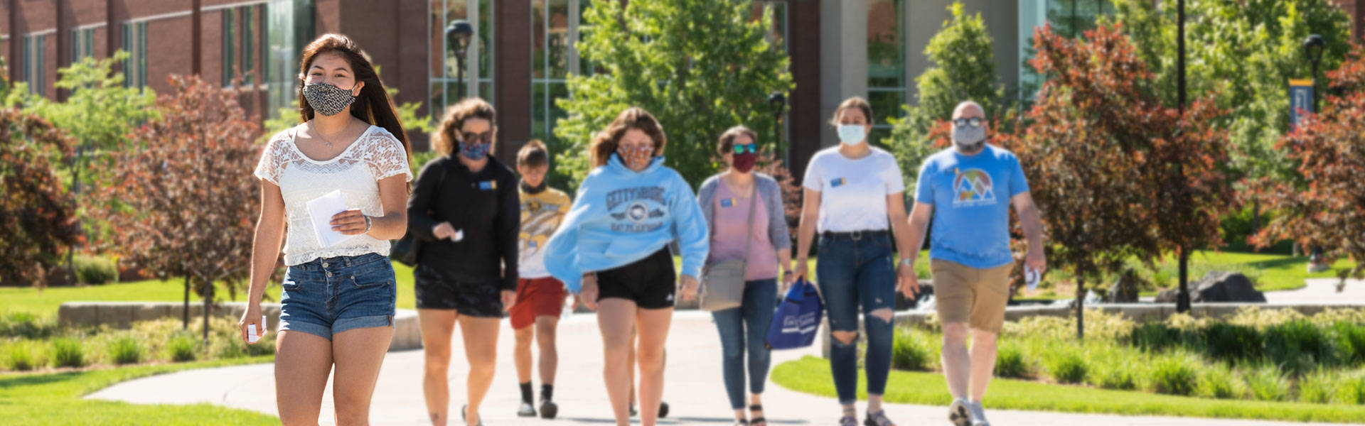 Student in mask leading campus tour on a bright sunny day.