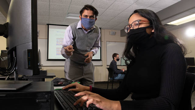 Dr. Rahul Gomes, assistant professor of computer science, talks with student researcher Avi Devy Mohan about their research, which is a collaborative project with Mayo Clinic Health System.