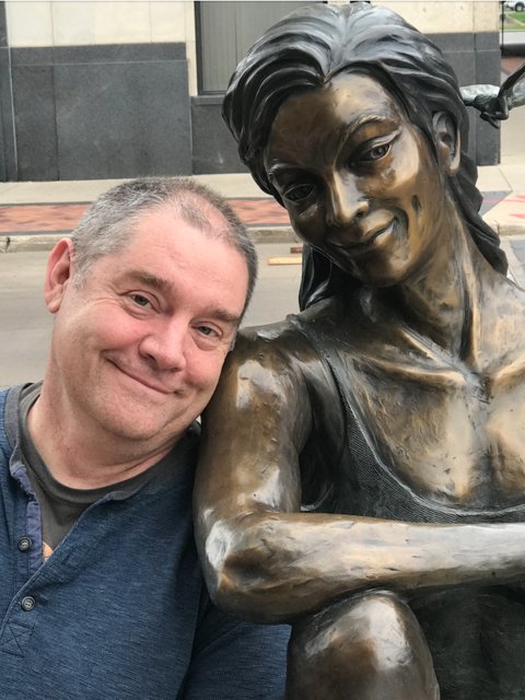 Man next to a statue of a woman