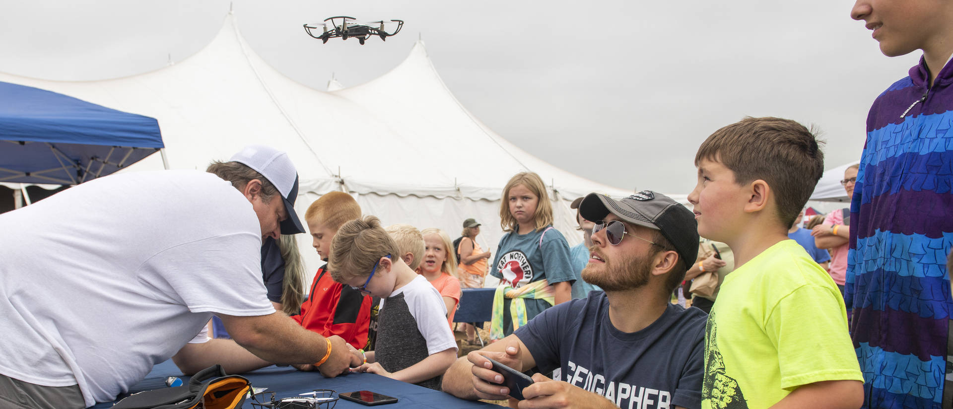 Kids and college student at toy drone table event