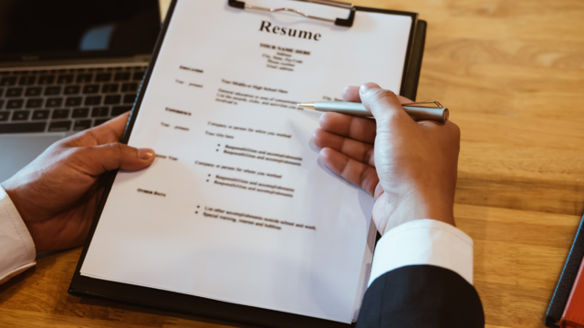 A person reviewing a printed resume