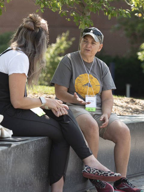 Cedar Marie talking to new faculty person outside in campus mall