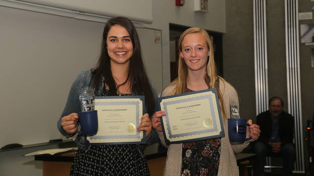 Two students hold their awards and smile at the camera.