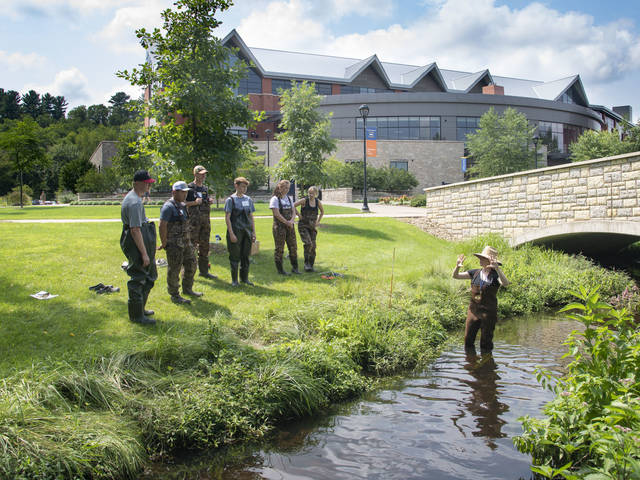 Hydrogeologist Dr. Sarah Vitale, an assistant professor of geology at UW-Eau Claire, explains stream flow measurement in Little Niagara Creek on campus to high school students who were part of a summer class on freshwater science. (Photo by Bill Hoepner)