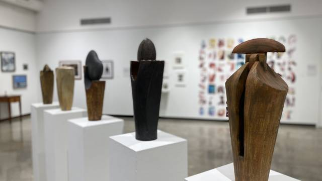 Installation view of art exhibition showing five ceramic sculptures on top of pedestals