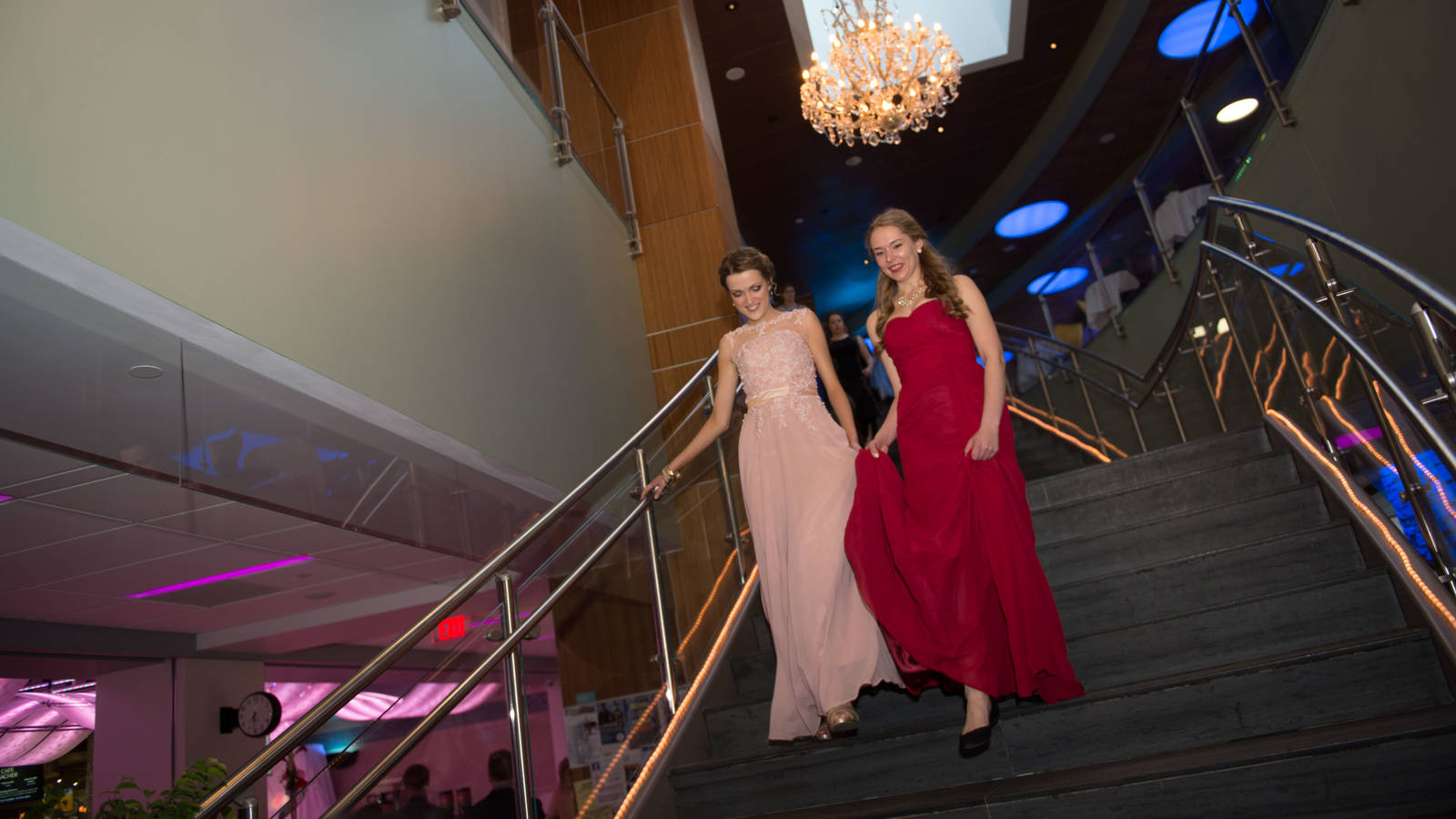 Two people walking down the staircase at the Viennese Ball at UW-Eau Claire