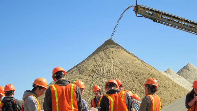 "UW-Eau Claire students enrolled in Dr. Brian Mahoney's ""Sedimentation and Stratigraphy"" class examine grains of sand during a tour of Wisconsin Industrial Sand Co.'s mining operations."