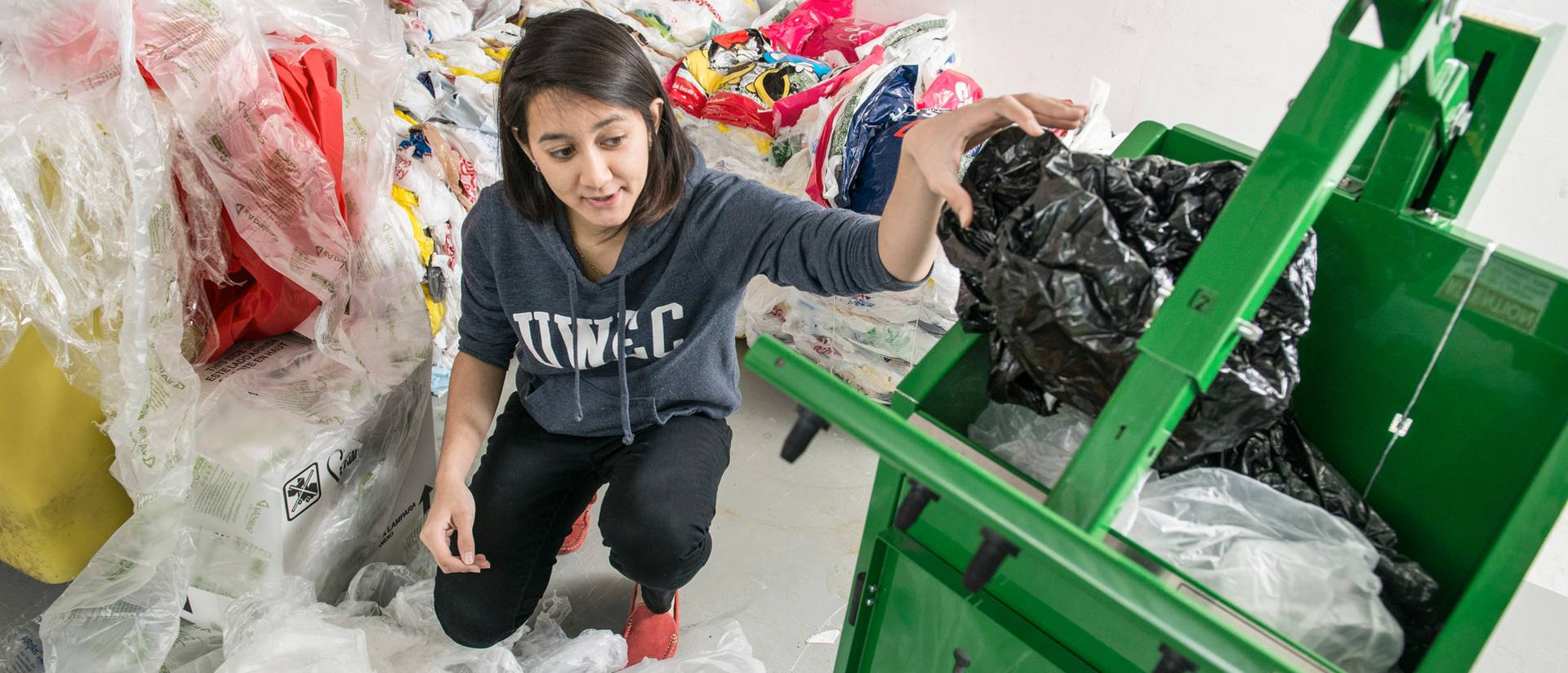 International student Amyline Sivathayalan, Malaysia, who works as a student recycler for Housing and Residence Life, sorts plastic bags and wrap and fills a machine that will bale the material so it can be recycled. She has made over 55 bales since fall.