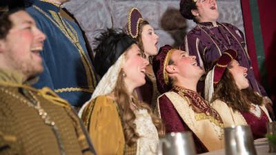 Members of the Ye Olde Madrigal Dinner laughing around the dinner table.