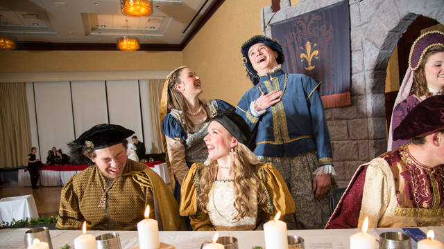 Members of the Ye Olde Madrigal Dinner laughing and talking.