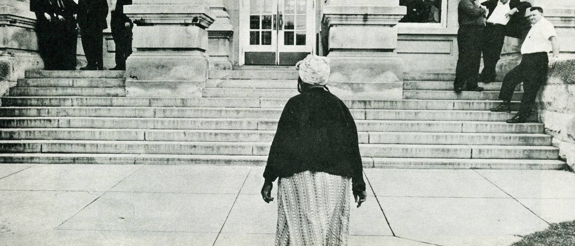 Solitary woman approaches courthouse
