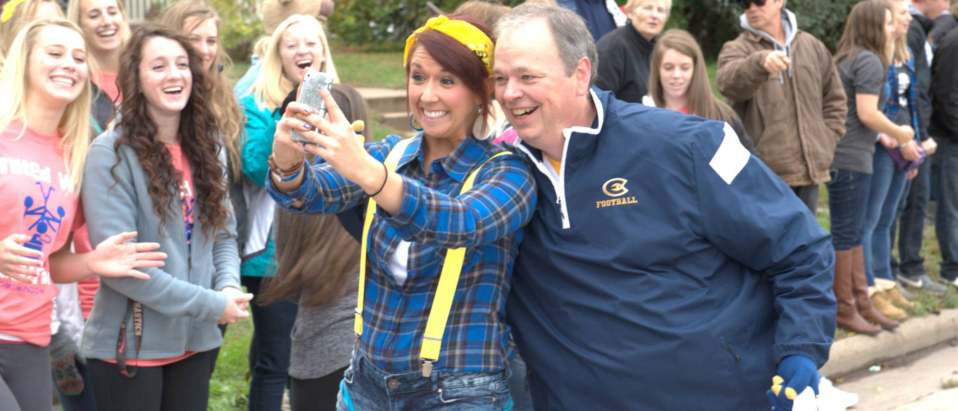 Chancellor James Schmidt with students along the parade route during Homecoming 2014.