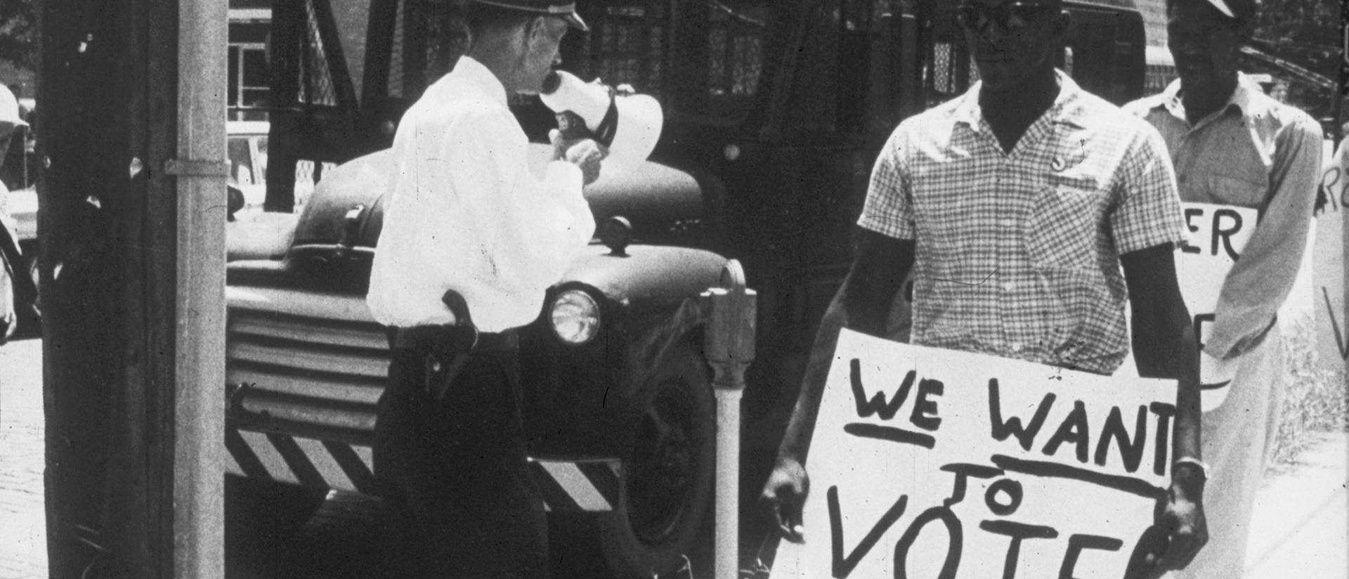 Historical photo from civil rights era, voting rights sign