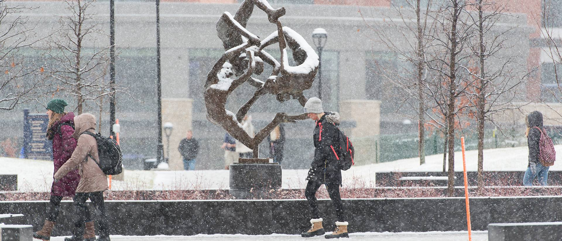 Students walking through campus on a snowy day