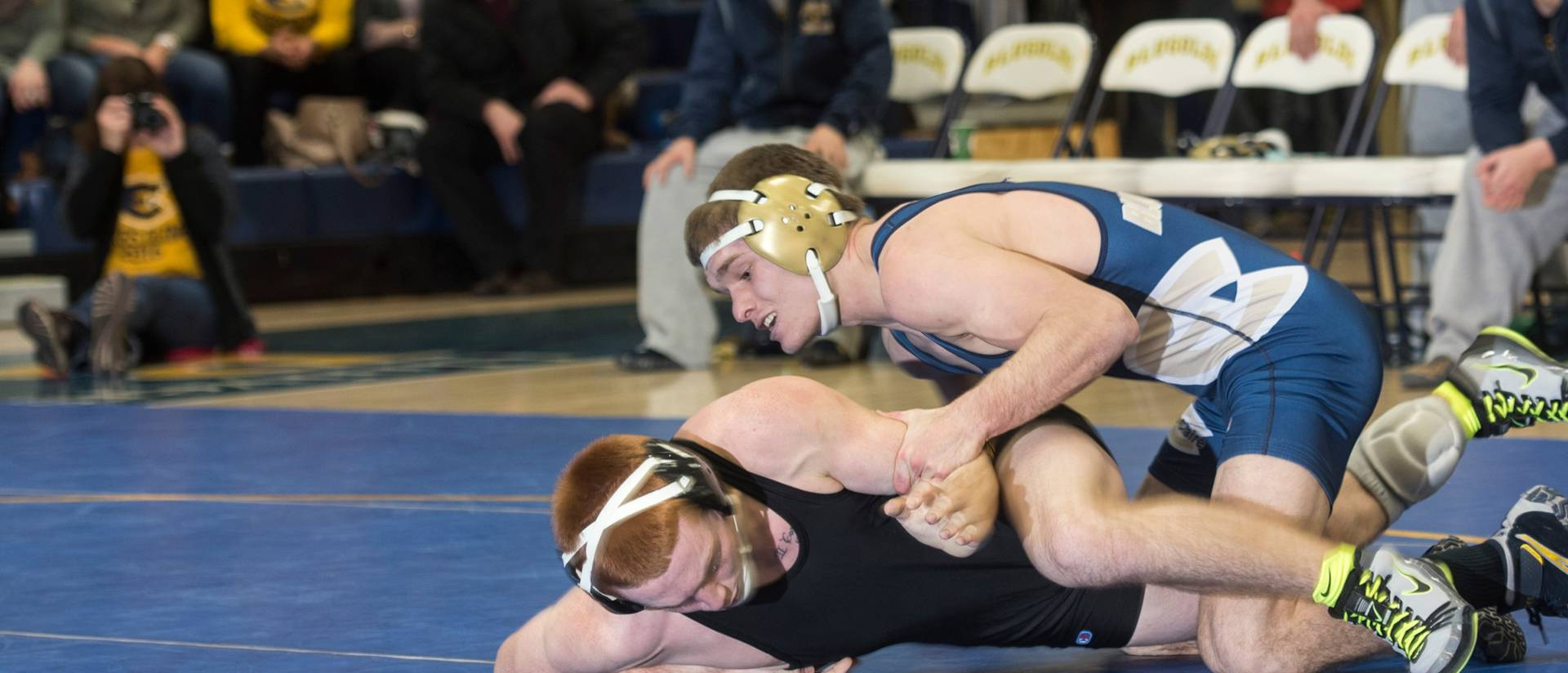 Blugold Nathaniel Behnke (in blue) during a wrestling match