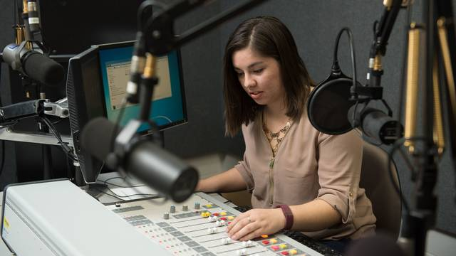 Journalism student in campus radio studio
