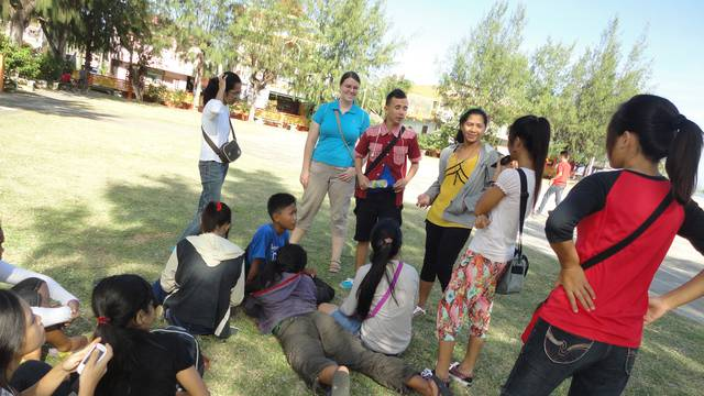 Heather Phelps (in blue shirt), a 2012 criminal justice graduate, working as a Peace Corps youth development volunteer in the Philippines.