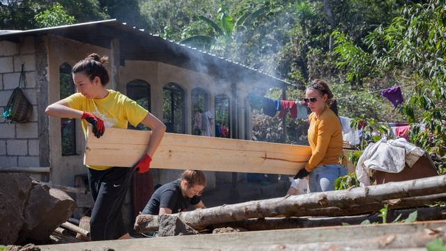 Blugolds Alyson Reum, left, and Ali Olmstead carry the lumber used to construct the walls for a new family home.