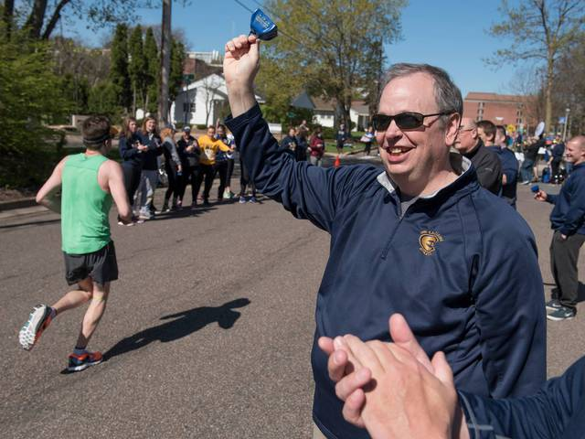 Chancellor Schmidt cheering on runners along the Blugold Mile
