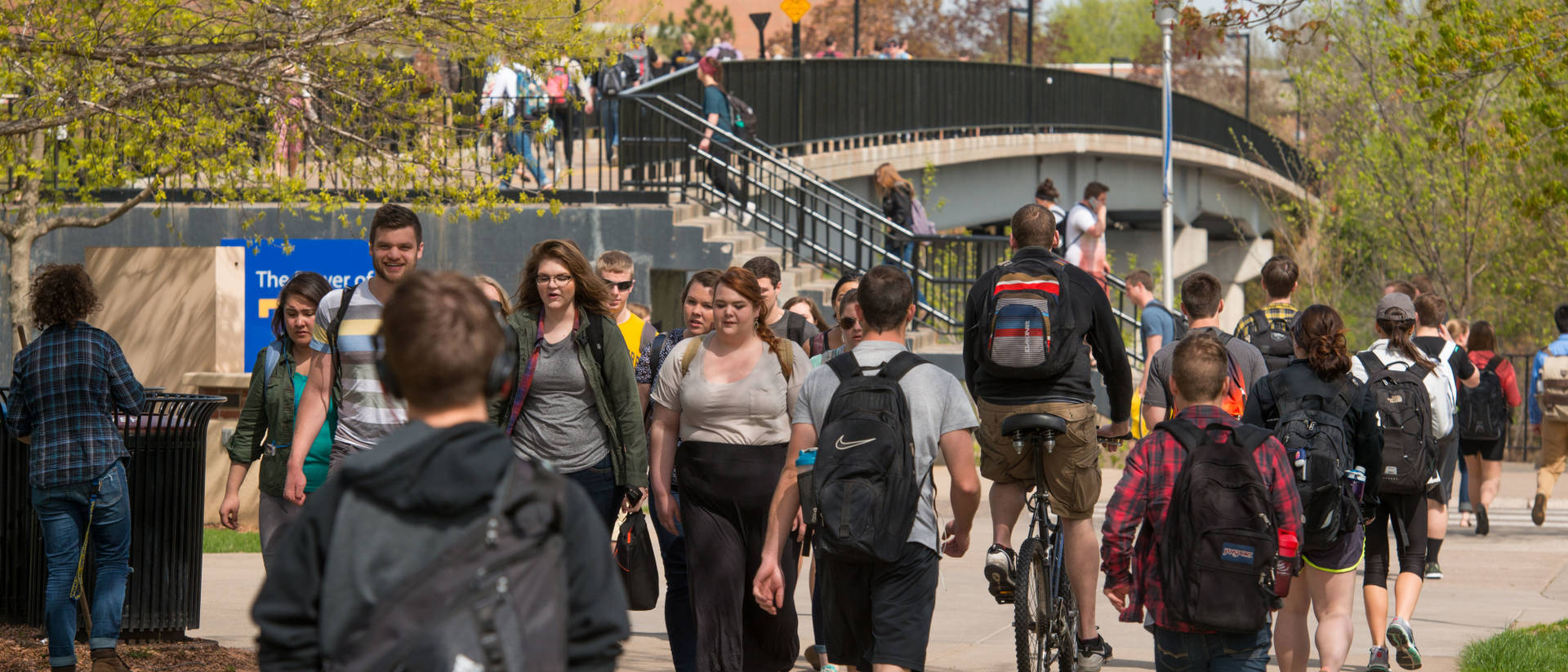 Students walking on campus sidewalks and the campus footbridge